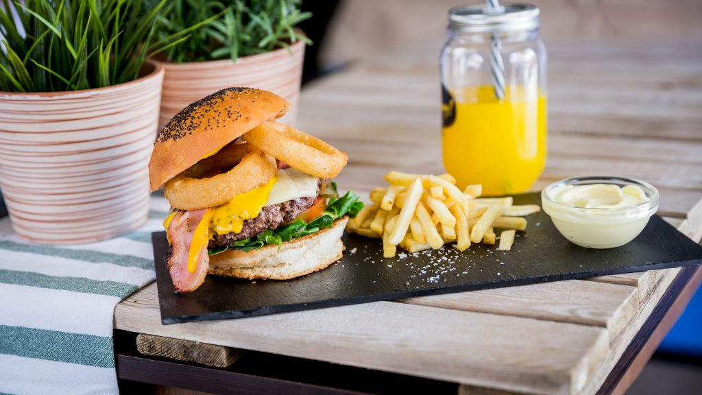 Vegan Burger Crispy Onion: Hamburguesa vegetal ,cebolla caramelizada, salsa, lechuga, tomate, cheddar vegano, mozzarella vegana, bacon vegano y aros crujientes de cebolla.