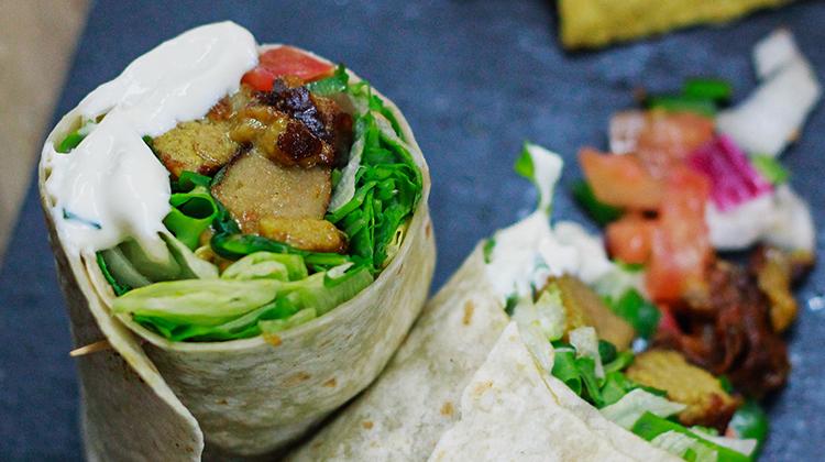 Nuevos platos veganos. Wrap Kebab de Seitán: Seitán macerado 24 horas en un aliño de yogur vegetal, especias de oriente medio y ralladura de naranja, lechuga, tomate, cebolla y salsa Wrap.