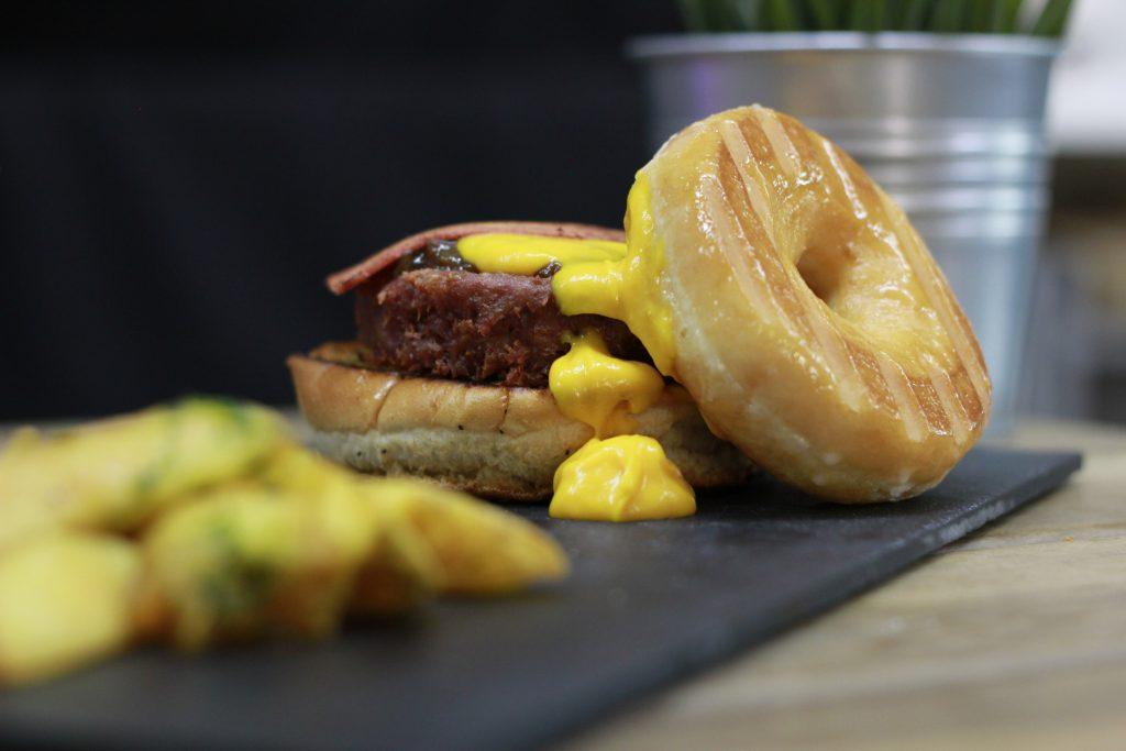 Nuevos platos veganos. Vegan Donut Burger: Bacon vegano, quesos havarti y cheddar veganos fundidos, cebolla caramelizada y lo mejor, ¡sustituimos el pan superior por un esponjoso Donut vegano!