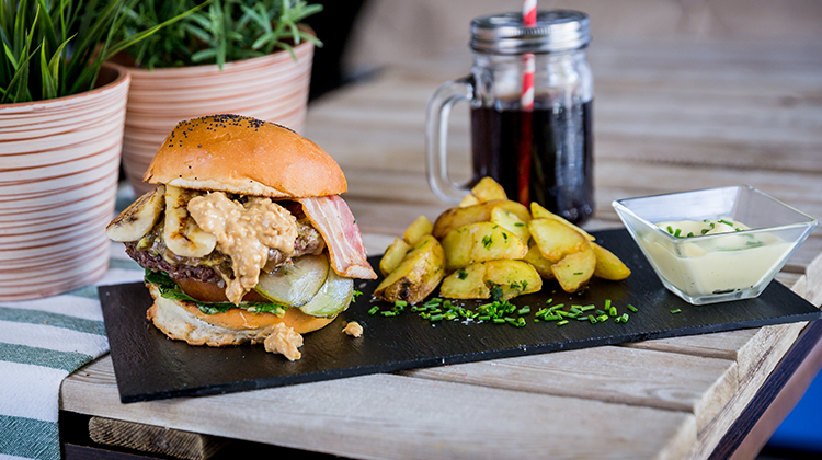 Nuevos platos veganos. Memphis burger: Hamburguesa de ternera con cebolla caramelizada, lechuga, tomate, pepinillo, bacon plátano a la plancha y crema de cacahuete como toque final.