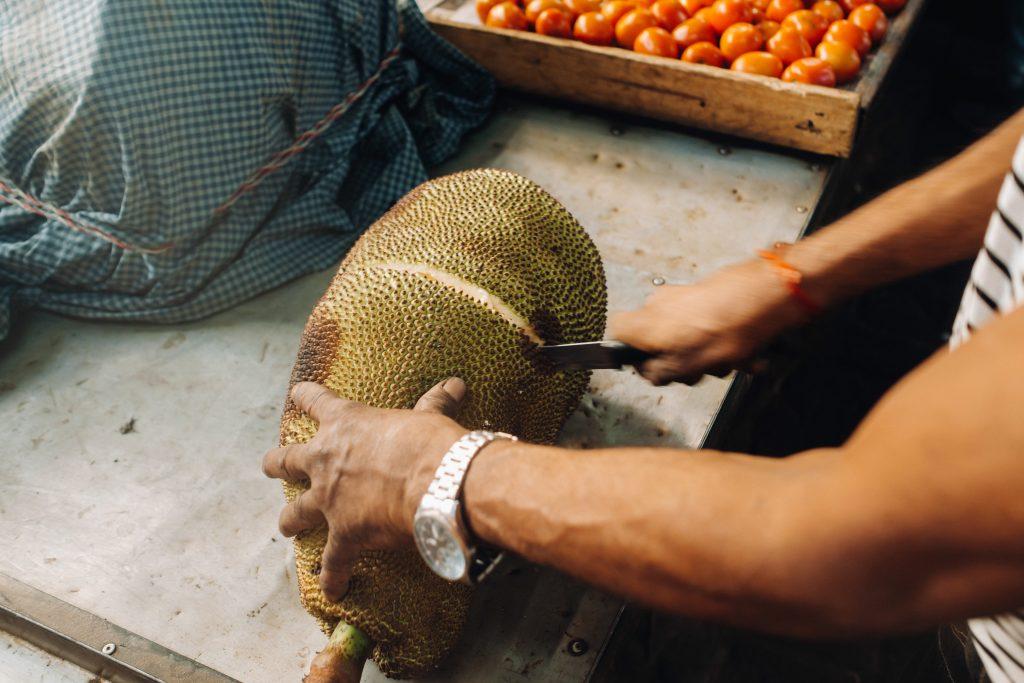 mujer asiática cortando jackfruit por la mitad